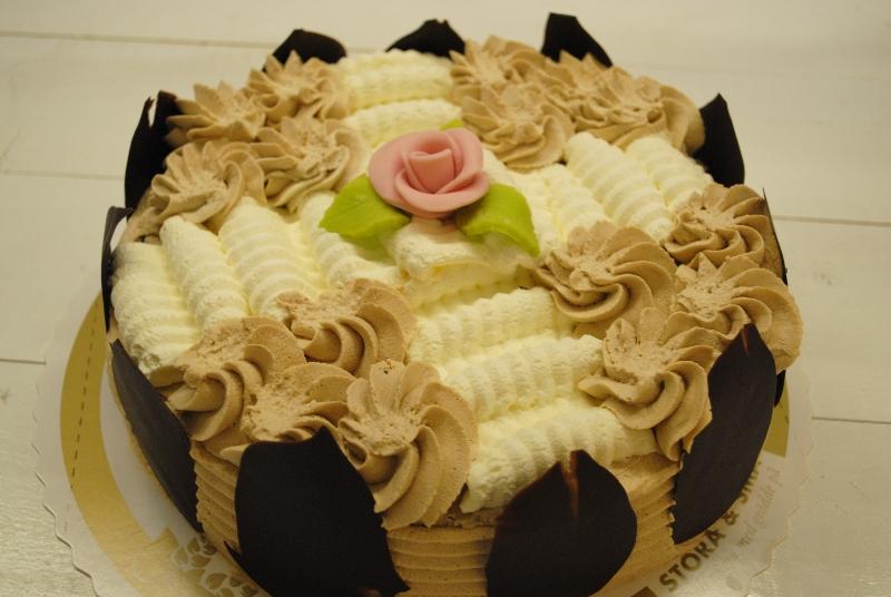 Moccatårta - Marängbottnar med chokladöverdrag, smaksatt grädde eller smörkräm. Chokladblad.